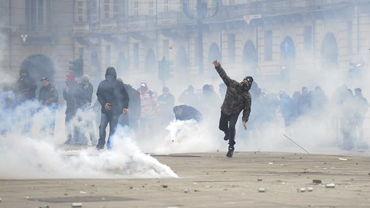 A protester throws a stone during a protest in downtown Turin