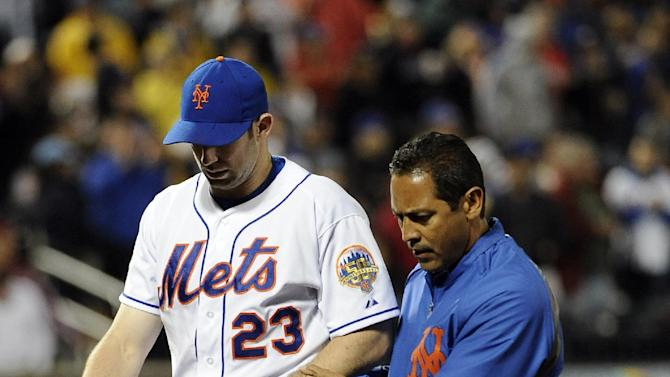 New York Mets right fielder Mike Baxter (23) is escorted off the field by head trainer Ray Ramirez after being injured when he crashed against the outfield wall to catch a fly ball by St. Louis Cardinals' Yadier Molina in the seventh inning of a baseball game on Friday, June 1, 2012, at Citi Field in New York. (AP Photo/Kathy Kmonicek)
