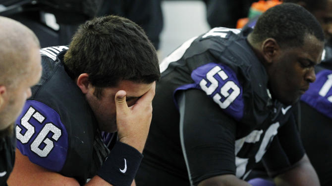 FILE - In this Oct. 6, 2012, file photo, TCU center Joey Hunt (56) sits on the bench with offensive tackle Tayo Fabuluje (59) during the final seconds of their 37-23 loss to Iowa State in an NCAA college football game in Fort Worth, Texas. With the realignment of conferences the past few years, it often means adjusting to a new style of football for teams that are switching. TCU had been a BCS buster before leaving the Mountain West Conference for the Big 12. The team is already bowl eligible, but it has four losses, all in conference_ which could leave them under .500 in conference for the first time since going 3-5 in Conference-USA in 2004. (AP Photo/LM Otero, File)