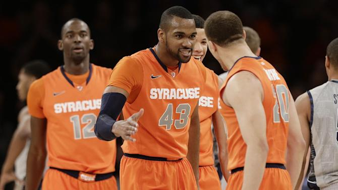 Syracuse's James Southerland  celebrates with teammate Brandon Triche after being fouled on a three-point basket during the first half of an NCAA college basketball against the Georgetown at the Big East Conference tournament Friday, March 15, 2013, in New York. (AP Photo/Frank Franklin II)