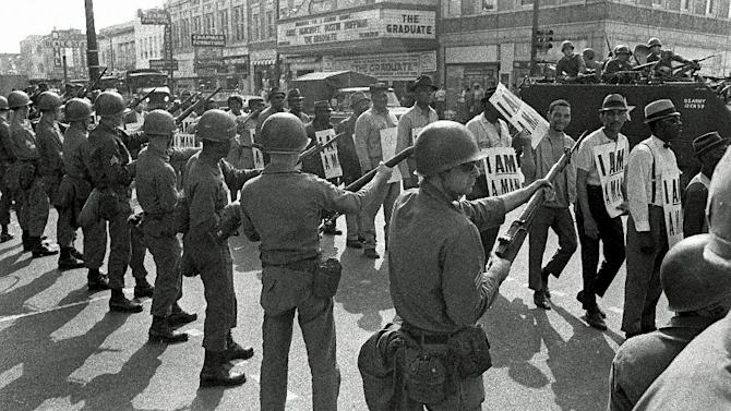 FILE -In this March 29, 1968 file photo, Striking sanitation workers and their supporters are flanked by bayonet-wielding National Guard troops and armored vehicles during a march on City Hall in Memphis, Tenn., one day after a similar march erupted in violence, leaving one person dead and several injured. Forty-five years after Martin Luther King Jr. was killed supporting a historic sanitation workers strike in Memphis, the city's garbage and trash collectors are fighting to hold on to jobs that some city leaders want to hand over to a private company. (AP Photo/Charlie Kelly, File)