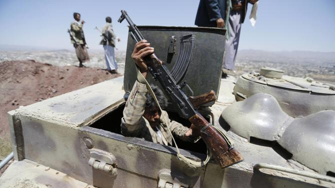 A Shi'ite Houthi rebel holds his weapon as he enters a tank at the compound of the army's First Armoured Division, after they took over it, in Sanaa