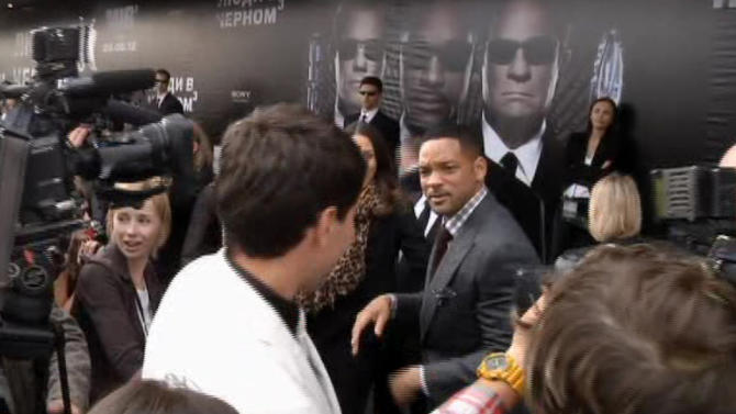 """In this video image taken from AP video U.S. actor Will Smith, center right, walks away from reporter Vitalii Sediuk, white suit, from the Ukrainian television channel 1+1 after slapping him on the red carpet before the premiere of """"Men in Black III"""" Friday May 18, 2012 in Moscow. Hollywood star Will Smith has slapped a male television reporter who tried to kiss him before the Moscow premiere of """"Men in Black III."""" Smith pushed him away and then slapped him lightly across the cheek with the back of his left hand.   (AP Photo via AP video)"""