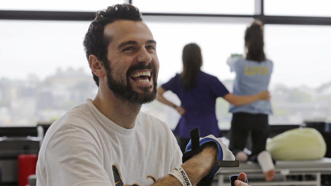 """In this Wednesday, May 22, 2013 photo, Boston Marathon bombing survivor Pete DiMartino, of Rochester, N.Y., smiles during a physical therapy session at the Spaulding Rehabilitation Hospital in Boston. DiMartino was injured in an explosion near the finish line, which blew away much of one leg and burned the other. """"I don't want anybody feeling sorry for me,"""" he said. """"... I want people to see that this has made me a better person and I want people to become better people through what they see through me."""" (AP Photo/Charles Krupa)"""