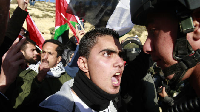Israeli police arrest a Palestinian activist at an area known as E-1 near Jerusalem, Tuesday, Jan. 15, 2013. Palestinian activists erected tents in the area known as E-1 last week to protest Israeli plans for a new settlement in the strategic West Bank location near Jerusalem. (AP Photo/Nasser Shiyoukhi)