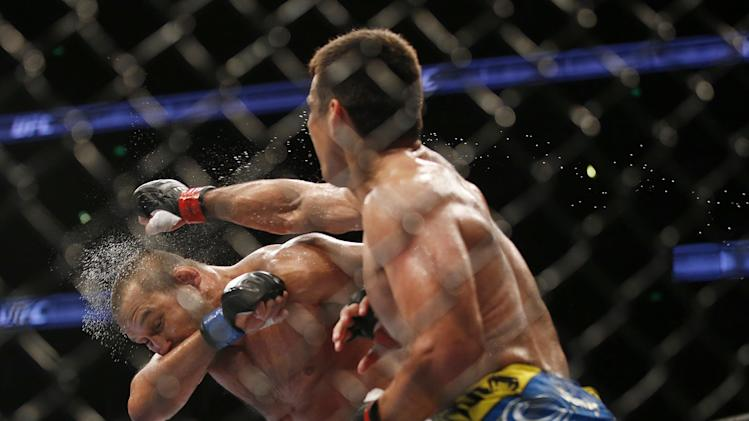 Lyoto Machida, right, of Brazil, lands a punch to the face of  Dan Henderson during their UFC 157 light heavyweight mixed martial arts match in Anaheim, Calif., Saturday, Feb. 23, 2013. Machida won by split decision after the third round. (AP Photo/Jae C. Hong)