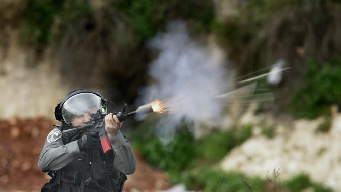 Isreali border policeman fires rubber bullets during a protest to support Palestinian prisoners, outside Ofer, an Israeli military prison near the West Bank city of Ramallah, Friday, Feb. 22, 2013. Israel holds a few thousand Palestinians on charges ranging from throwing rocks to deadly attacks. (AP Photo/Majdi Mohammed)