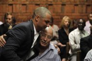 Oscar Pistorius' brother Carl hugs his father Henke during a break in court proceedings at the Pretoria Magistrates court, February 21, 2013. REUTERS/Mike Hutchings