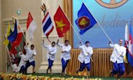 Performers carry flags of ASEAN member countries during a ceremony marking the 45th anniversary of the Association of Southeast Asian Nations (ASEAN) and its 20th summit in Phnom Penh on April 3, 2012. Southeast Asian leaders are expected Wednesday to issue a formal call for the West to ease sanctions on Myanmar
