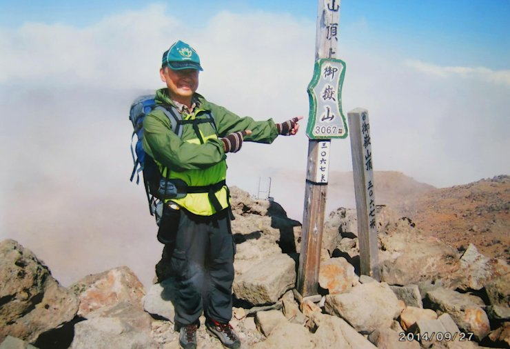 In this Saturday, Sept. 27, 2014 file photo found in a camera possessed by 59-year-old hiker Izumi Noguchi, a construction worker, who fell victim to the eruption of Mount Ontake, and was offered to Kyodo News by his wife, Hiromi, Friday, Oct. 3, Noguchi poses on the summit of Mount Ontake shortly before the eruption of the volcanic mountain in central Japan. (AP Photo/Kyodo News)  Click photo to view slideshow.