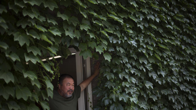 "Artist Ai Weiwei poses for photos at a door of his studio in Beijing, China, Wednesday, May 22, 2013. Ai's music video accompanying his heavy metal single ""Dumbass'' released Wednesday depicts an insensitive, overbearing state power that tramples on individual rights. The video is meant to reconstruct his 81-day secret detention in 2011, which was part of the overall crackdown by Chinese authorities on dissent. Ai later was convicted of tax evasion, which his supporters saw as punishment for his activism. (AP Photo/Alexander F. Yuan)"