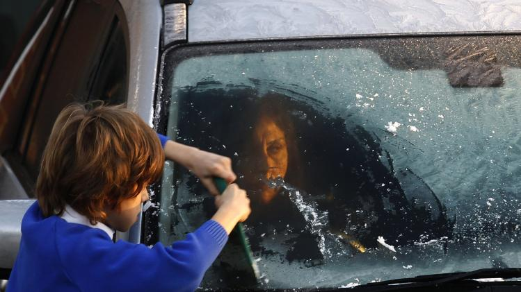 A young boy scrapes ice off his mother's windscreen on a frosty morning in west London