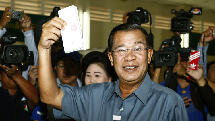 FILE - In this July 28, 2013 file photo, Cambodia's Prime Minister Hun Sen shows his ballot at a polling station in Takhmau town, south of Phnom Penh, Cambodia. The two rival parties claiming victory in Cambodia's general election reached an agreement Saturday, Aug. 3, 2013 with the state National Election Committee to investigate polling irregularities, a move that could smooth the way to ending the country's political deadlock. Hun Sen, in power for 28 years, has made clear that he believes the final results, due in mid-August, will favor him and that he will have another five-year term in office. With his overpowering influence over the state apparatus and the judiciary, he is almost certain to have his way. (AP Photo/Heng Sinith, File)