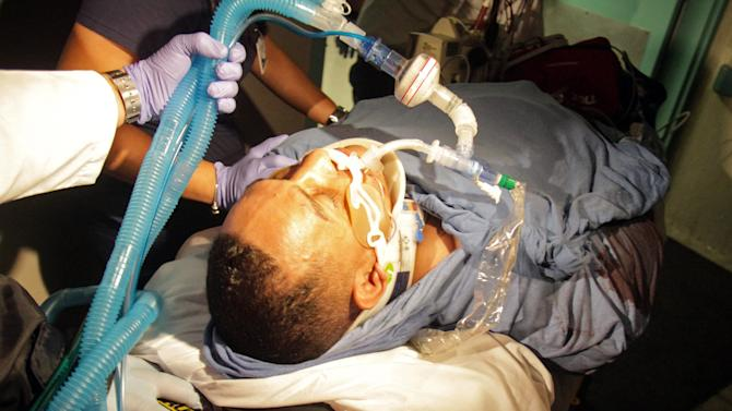 """Former world boxing champion Hector """"Macho"""" Camacho, of Puerto Rico, is taken by paramedics inside a medical center in San Juan, Puerto Rico, Tuesday, Nov. 20, 2012. Camacho, 50, was shot in the face as he sat in a car at his hometown of Bayamon, one of the cities that make up the San Juan metropolitan area and doctors said he was in critical but stable condition, expected to survive. (AP Photo/GFR Media, Primera Hora/El Nuevo Dia, Sebastian Perez)"""