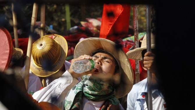 Student protester drinks water as they sit on the street during a protest against an education bill in Letpadan