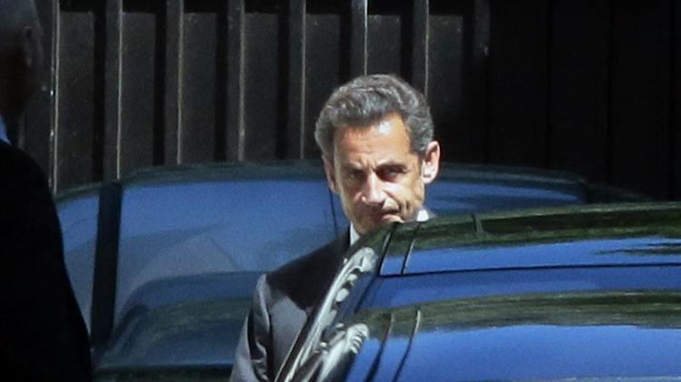 Former French president Nicolas Sarkozy leaves his home in Paris, on July 2, 2014