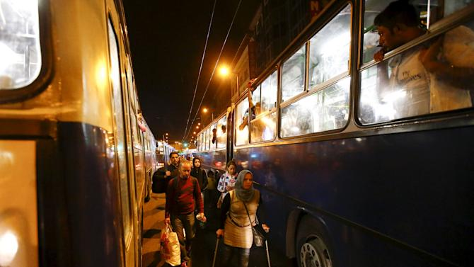 Migrants walk to board a bus bound for Austria and Germany, next to the Keleti train station in Budapest
