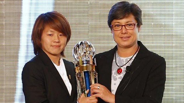 Japan's football player Aya Miyama (L) holds her trophy as she poses with AFC Vice President Moya Dodd after winning the AFC Women's Player of the Year award in 2012 (Reuters)
