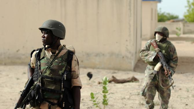Nigerian soldiers patrol in the north of Borno state close to a former Boko Haram camp on June 5, 2013