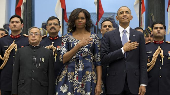 President Barack Obama, right, first lady Michelle Obama and Indian President Pranab Mukherjee, left, stand during the US National Anthem before a receiving line at the State Dinner at the Rashtrapati Bhavan, the presidential palace, in New Delhi, India, Sunday, Jan. 25, 2015. Obama's arrival Sunday morning in the bustling capital of New Delhi marked the first time an American leader has visited India twice during his presidency. Obama is also the first to be invited to attend India's Republic Day festivities, which commence Monday and mark the anniversary of the enactment of the country's democratic constitution. (AP Photo/Carolyn Kaster)