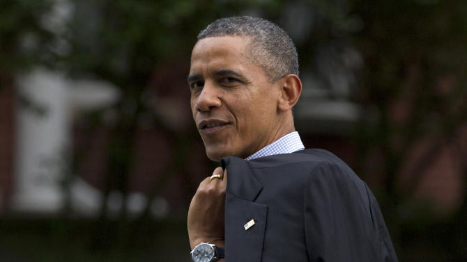 President Barack Obama glances back as he walks through his Hyde Park neighborhood to a campaign event, Sunday, Aug. 12, 2012, in Chicago. (AP Photo/Carolyn Kaster)
