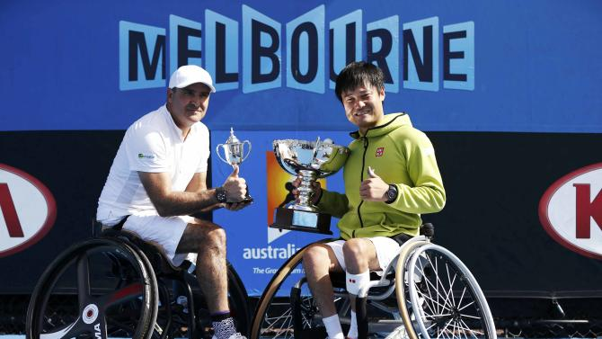 Kunieda of Japan and Houdet of France pose with their trophies after their men's wheelchair singles final match at the Australian Open 2015 tennis tournament in Melbourne