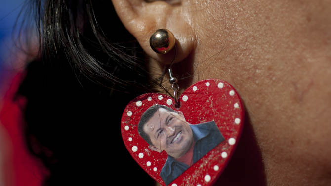 """A supporter of Venezuela's President Hugo Chavez wears earrings she decorated with an image of Chavez as she attends a rally in Caracas, Venezuela, Thursday, Jan. 10, 2013. The government organized the unusual show of support for the cancer-stricken leader on the streets outside Miraflores Palace on what was supposed to be his inauguration day. Chavez has been fighting an unspecified type of pelvic cancer since June 2011 and has undergone repeated surgeries, chemotherapy and radiation treatments. The government said in its last update on Monday that Chavez was in a """"stable situation"""" while being treated for a severe respiratory infection. The government has hasn't said how severe his """"respiratory deficiency"""" is. (AP Photo/Ariana Cubillos)"""
