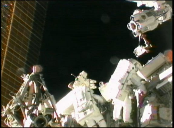 Spacewalking astronauts Sunita Williams (left) and Akihiko Hoshide (right) work outside the INternational Space Station near the outpost's robotic arm on Sept. 5, 2012.