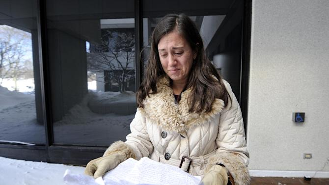 With tears in her eyes, Pirscilla Arena, 41, from Mount Sinai, N.Y., reads letters she wrote to her two children as she spent the night in her car on North Ocean Avenue in Farmingville after the car got stuck in the snow while she was traveling home after work during yesterday's snow storm. Arena was at the Brookhaven Town Hall after being rescued by a N.Y. State Trooper on Saturday, Feb. 9, 31, 2013 in , N.Y. (AP Photo/Kathy Kmonicek)