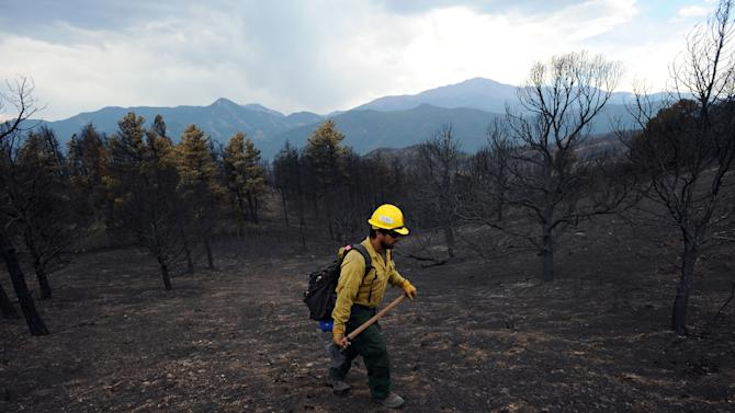 "A firefighter from King Canyon National Park in California walks through a burned-out area of Colorado Springs, Colo., Friday, June 29, 2012. After declaring a ""major disaster"" in the state early Friday and promising federal aid, President Barack Obama got a firsthand view of the wildfires and their toll on residential communities. More than 30,000 people have been evacuated in what is now the most destructive wildfire in state history. (AP Photo/The Gazette, Christian Murdock)"
