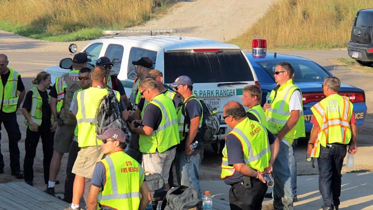 Searchers gather outside a ranger station at Sleeping Bear Dunes National Lakeshore in northern Michigan, where a search was underway for a man and his three children Monday, Aug. 26, 2013. The man, who is wanted on a domestic violence charge, and his children have been found safe. (AP Photo/John Flesher)