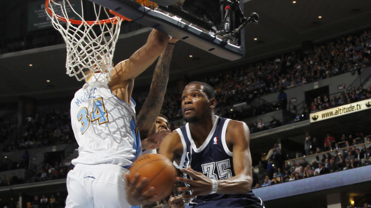 Oklahoma City Thunder forward Kevin Durant, right, goes up for a reverse layup past Denver Nuggets forward JaVale MGee in the first quarter of an NBA basketball game in Denver on Friday, March 1, 2013. (AP Photo/David Zalubowski)