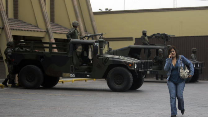 In this Jan. 9, 2008 file photo, a woman walks past Mexican army soldiers guarding a hotel in the city of Reynosa, in the state of Tamaulipas, northern Mexico. On March 10, 2013, heavy gunfire echoed along the main thoroughfare and across several neighborhoods in a firefight that lasted for hours, leaving perforated and burned vehicles scattered across the border city. Social media exploded with reports of dozens dead. Witnesses saw at least 12, but an official count showed only a couple of deaths. (AP Photo/Dario Lopez-Mills, File)