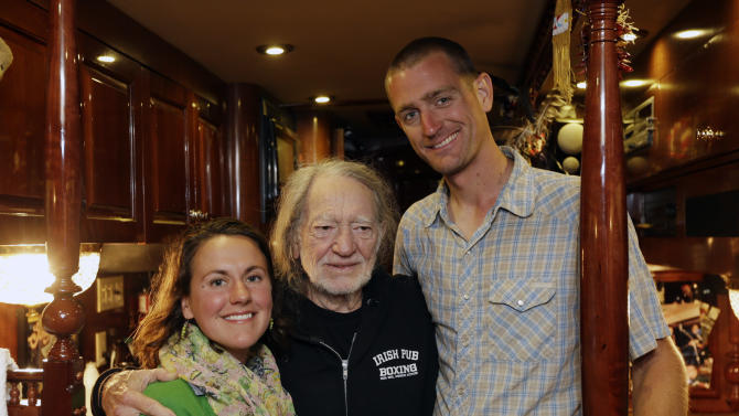 Country music artist Willie Nelson, center, poses with organic farmer Cara Fraver, left, and her husband Luke Deikis of Quincy Farm in Easton, N.Y., on his tour bus on Thursday, June 13, 2013, in Colonie, N.Y. Nelson is taking his annual Farm Aid benefit concert to upstate New York with an all-day festival of music and locally grown food in September. (AP Photo/Mike Groll)