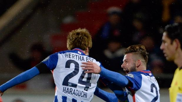 Hertha's midfielder Genki Haraguchi (L) celebrates scoring with his team-mate defender Marvin Plattenhardt during the German Cup quarter final football match Heidenheim vs Hertha Berlin on February 10, 2016 in Heidenheim, Germany