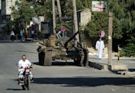 A Syrian man rides a motorcycle past an army tank on which children play, parked along a street in Aazaz, in northern Syria. Syrians joined prayers and staged demonstrations for Eid, taking place for the second year under the shadow of a conflict the Observatory says has now claimed 23,000 lives while the UN gives a death toll of 17,000