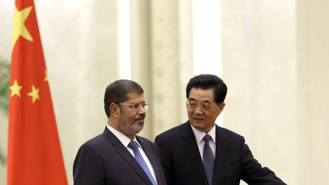 Egyptian President Mohammed Morsi, left, is shown the way by Chinese President Hu Jintao during a welcome ceremony held at the Great Hall of the People in Beijing Tuesday, Aug. 28, 2012. China is hosting Egypt's newly elected president despite its uneasiness with the Arab Spring revolution that helped bring him to power, while the new leader seeks to shore up his country's flagging economy. (AP Photo/Ng Han Guan)