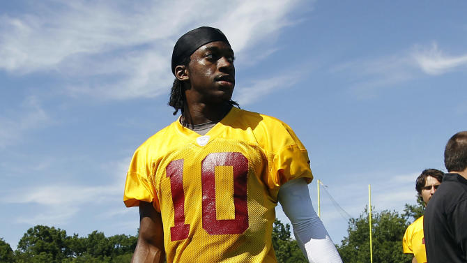 """FILE - In this June 13, 2012, file photo, Washington Redskins quarterback Robert Griffin III walks off the field following NFL football practice in Ashburn, Va. Former Baylor basketball player Richard Khamir Hurd is facing federal extortion charges for allegedly threatening to release """"derogatory information"""" about Griffin. Hurd made his first appearance Monday, June 25, in federal court in Waco, Texas. (AP Photo/Pablo Martinez Monsivais, File)"""