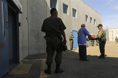 An inmate is checked by guards after leaving a general population cell block, in Corcoran State Prison, California