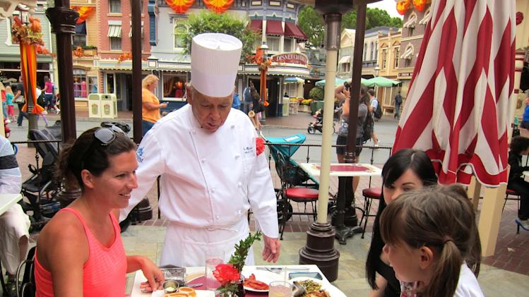 In this photo taken Sept. 20, 2013, Oscar Martinez, 77, center, greets diners at the Carnation Cafe at Disneyland in Anaheim, Calif. The chef is the park's longest-tenured employee, beginning as a busboy nearly 57 years ago. He says he loves his job, and a new poll from the Associated Press-NORC Center for Public Affairs finds he's not alone: Nine out of ten workers 50 and older say they're satisfied with their work. (AP Photo/Matt Sedensky)