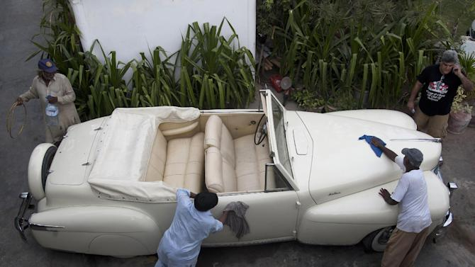 In this photo taken May 10,  2015, Pakistani workers clean a Lincoln classic vintage car in Karachi, Pakistan. For an elite but passionate group of vintage car collectors in Pakistan, restoring antique rides is like traveling back in time and money seems to be no obstacle when the prize is a Lincoln convertible that belonged to an Afghan king or a Rolls-Royce once used by India's last viceroy. (AP Photo/Shakil Adil)
