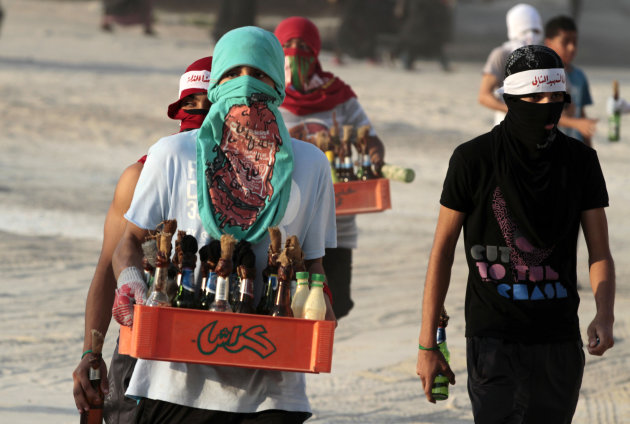 Masked Bahraini anti-government protesters carry crates of homemade paint and petrol bombs into clashes with riot police in Sanabis, Bahrain, on Friday, Oct. 5, 2012. Riot police used water cannons an