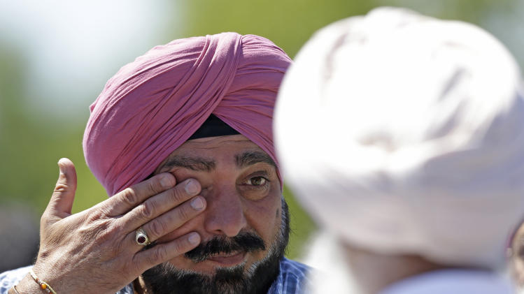 FILE - In this Sunday, Aug 5, 2012 file photo, a man wipes away tears outside a Sikh temple in Oak Creek, Wis. after a shooting. A white supremacist killed six worshippers and injured four other people before taking his own life. (AP Photo/Jeffrey Phelps)