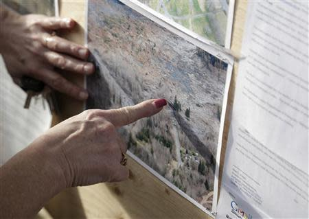 Neal inspects aerial photos of massive landslide for any signs of her missing husband in Darrington