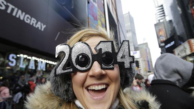 FILE - This Dec. 31, 2013, file photo shows Veronica Boshen of Allentown, PA., in her 2014 glasses while waiting for the ball drop celebration to begin in Times Square on New Year's Eve, in New York. Americans are closing out 2014 on an optimistic note, according to a new Associated Press-Times Square Alliance poll. Nearly half predict that 2015 will be a better year for them than 2014 was, while only 1 in 10 think it will be worse. There's room for improvement: Americans give the year gone by a resounding 'meh.' (AP Photo/Kathy Willens, File)