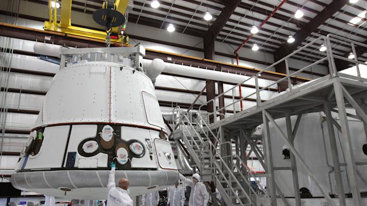 In this Nov. 16, 2011, photo provided by NASA, the SpaceX Dragon capsule is lifted to be placed atop its cargo ring inside a processing hangar at Cape Canaveral Air Force Station in Florida. The first commercial cargo run to the International Space Station has been delayed again for more software testing.  Space Exploration Technologies Corp., better known as SpaceX, was aiming for a Monday, April 30, 2012, liftoff of its Falcon rocket and Dragon capsule. But on Wednesday, May 2, the California-based company announced its latest postponement and said a new launch date had not been set. (AP Photo/NASA, Kim Shiflett)