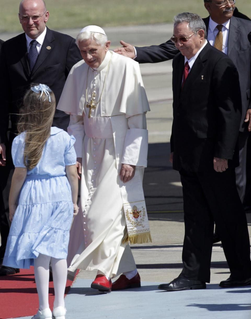 Pope Benedict XVI walks with Cuba's President Raul Castro, right, as he arrives to Antonio Maceo airport in Santiago de Cuba, Cuba, Monday March 26, 2012. (AP Photo/Ramon Espinosa)