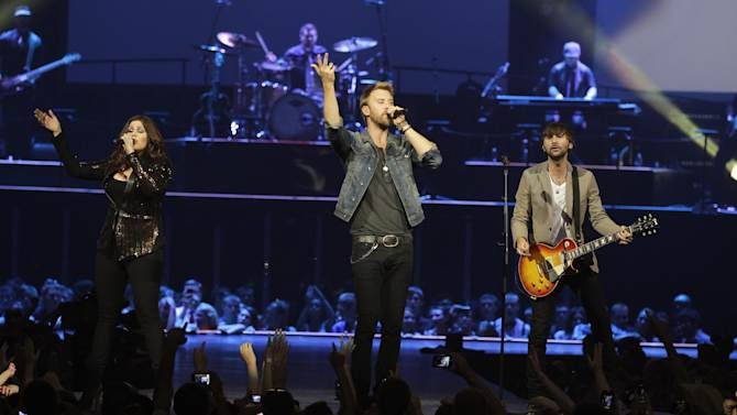 "Lady Antebellum's Hillary Scott, Charles Kelly and Dave Haywood perform  Wednesday, May 16, 2012, in Louisville, Ky. The Grammy-winning Lady Antebellum trio will staged a ""mini-prom"" bash for students from Henryville Junior-Senior High School, followed by a benefit for the devastated community. (AP Photo/Darron Cummings)"