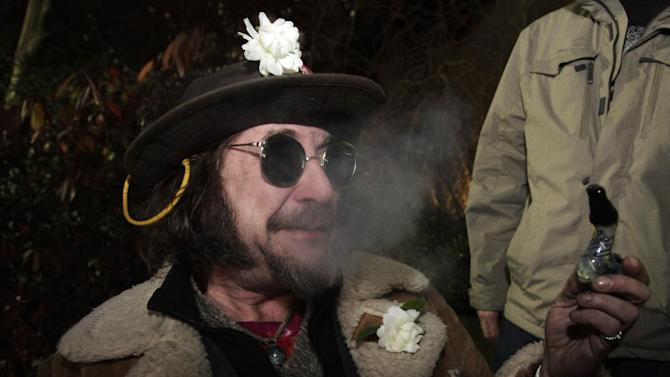 "A man known as ""Professor Gizmo,"" smokes marijuana in a glass pipe, Wednesday, Dec. 5, 2012, just before midnight at the Space Needle in Seattle. Possession of marijuana became legal in Washington state at midnight, and several hundred people gathered at the Space Needle to smoke and celebrate the occasion, even though the new law does prohibit public use of marijuana. (AP Photo/Ted S. Warren)"