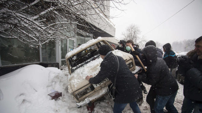 In this photo taken on Friday, March 15, 2013, members of a pro-Kremlin youth group upturn the car that belongs to pushers of spice, a synthetic drug, in Moscow, Russia. Russian officials and anti-drugs campaigners say that spice has become one of the most dangerous drugs widely available to youngsters and almost impossible to ban because of the constantly changing chemical ingredients. (AP Photo/ Alexander Zemlianichenko Jr)